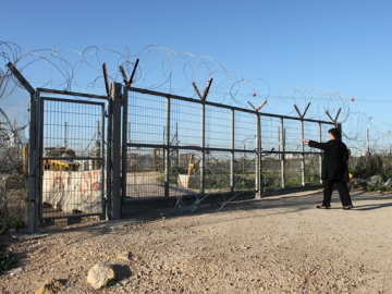 A woman describes the pain and injustice she feels at being cut off from her lands. This is a farmers gate. This gate only opens 3 times a day and a permit is required to pass through it. On the other side are Palestinian lands. If a family is granted a permit to tend their lands only one person will be allowed to cross for a limited period of time. The system has no regard for land rights or the size of the land. As a result many families who were at one time self-sufficient are now facing a life of poverty. Also many Palestinians fear that if their land is left unattended it will be defined uncultivated and after 3 years become 'state land'. Palestinians have no way to protect their lands from this.